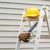 Stepladder, hardhat, gloves and hammer with house siding background